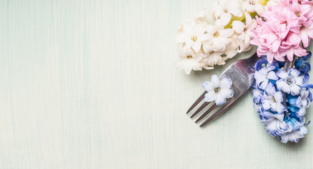 Fork with hyacinths flowers on light green background, top view, banner for website or placard. Place setting concept. Spring or Easter food.