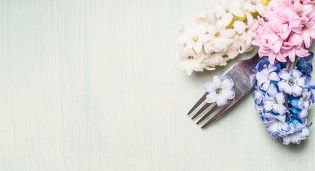 Gabel mit Hyazinthen Blumen auf hellgrünem Hintergrund, Draufsicht, Banner für Website oder Plakat. Einstellungskonzept setzen Frühling oder Ostern Essen.