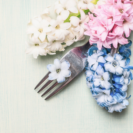 hyacinths: Fork with hyacinths flowers on light green background, top view, close up. Place setting concept. Spring or Easter food.