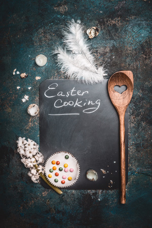 素朴なイースター料理背景黒板、ケーキ、卵はシェル ・ フォン ・ ウズラ、木のスプーンとヒヤシンスの花です。トップ ビューのテキスト