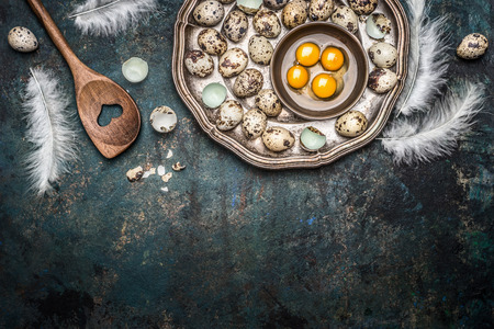 Quail eggs and cooking spoon on rustic background, top view, place for text