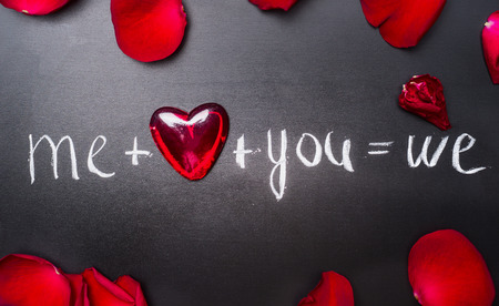 over white: Valentines day lettering background with red hearts and rose petals, top view. Me plus you equals we. Love symbols