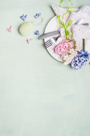 table top: Easter  table setting with plate, cutlery, lace doily napkin,  hyacinths flowers and decor egg on light shabby chic wooden background, top view, vertical