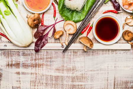 Asian cooking ingredients with chopsticks  on rustic wooden background, top view, place for text. Asian food concept.