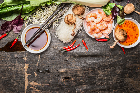 Aziatische kokende ingrediënten met soja en zoetzure saus en eetstokjes op rustieke achtergrond, bovenaanzicht. Aziatisch eten concept. Stockfoto