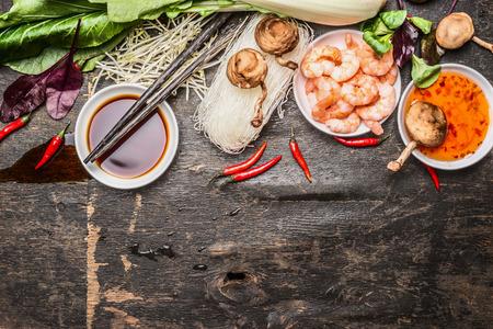 Ingredientes asiáticos de cocina con soja y agridulce salsa y los palillos en el fondo rústico, vista desde arriba. Concepto de comida asiática. Foto de archivo