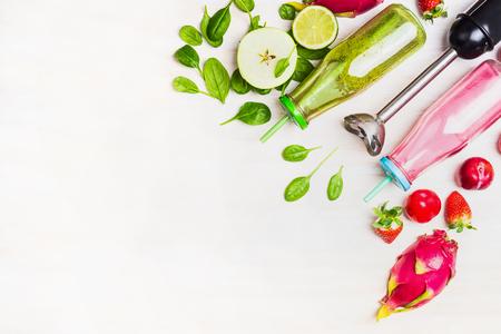 Grüne und rote Smoothie-Flaschen mit frischen Zutaten und elektrischen Mixern auf weißen Holz Hintergrund, Ansicht von oben, Grenze. Superfoods und Gesundheit oder Detox-Diät-Food-Konzept. Standard-Bild