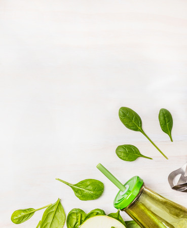 Green smoothie  in glass bottle with spinach leaves on white wooden background, top view, border. Superfoods and health or detox  diet food concept.