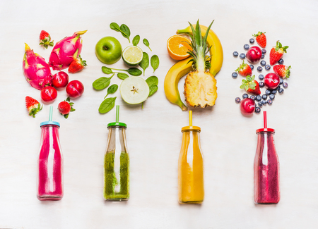 juice fresh vegetables: Assortment of fruit  and vegetables smoothies in glass bottles with straws on white wooden background. Fresh organic Smoothie ingredients. Superfoods and health or detox  diet food concept. Stock Photo