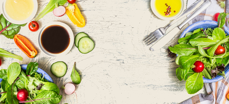 Tasty salad making with vegetables and dressing ingredients on light rustic background, top view, banner. Healthy lifestyle or detox diet food concept