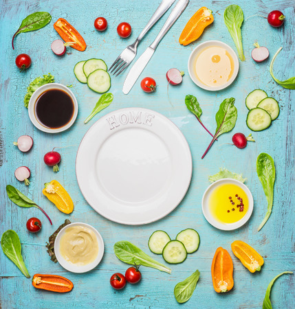 Fresh delicious salad and dressing ingredients around empty white plate on light blue background, top view, frame. Health salad making. Flat lay of healthy  lifestyle or detox diet food  concept