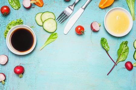 alimentos saludables: Preparación de la ensalada con los ingredientes cubiertos vestidores, lechuga, hierbas y verduras en el fondo de madera de color azul claro, vista desde arriba, el lugar de texto. estilo de vida saludable o de desintoxicación dieta concepto de alimentos Foto de archivo