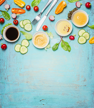 Salad making. Cutlery and dressing ingredients for fresh salad on light blue background, top view place for text. Vinegar ,mustard,oil and honey with chopped vegetables and lettuce leaves. Zdjęcie Seryjne