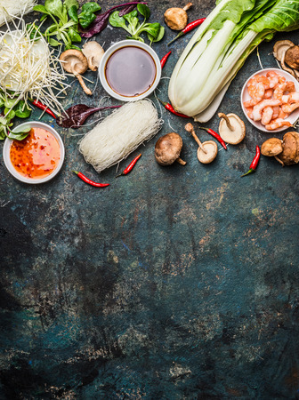Asian cooking ingredients: rice noodles, pok choy , sauces, shrimps, chili and Shiitake mushrooms on dark background, top view, place for text. Asian food concept: Chinese or Thai cuisine. Stock Photo