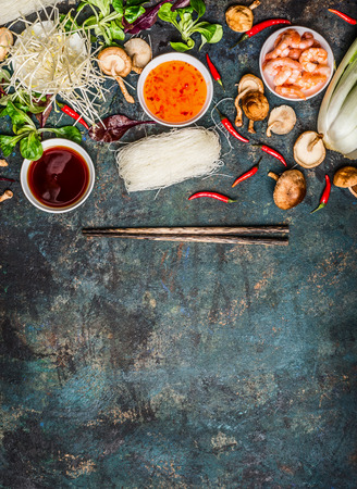 Various of asian cooking cooking ingredients and sauces with chopsticks  on rustic background , top view , place for text. Asian food concept: Chinese or Thai cuisine.