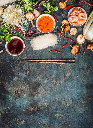 Verschiedene von der asiatischen Küche Kochen Zutaten und Saucen mit Stäbchen auf rustikalen Hintergrund, Ansicht von oben, Platz für Text. Asian Food-Konzept: Chinesisch oder Thai-Küche.