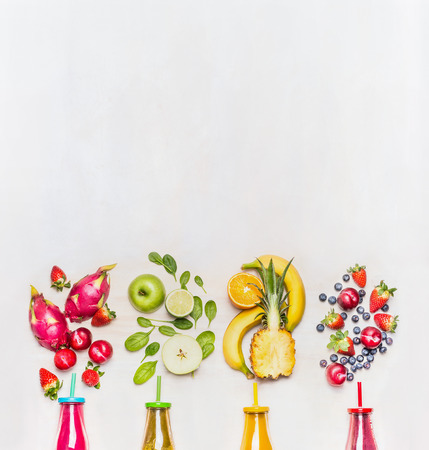 Healthy fruits smoothies with colorful ingredients  on white wooden background, top view, place for text.  Superfoods and healthy lifestyle or detox  diet food concept.