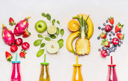 fruit juices: Bottles of Fruits smoothies with various ingredients on white wooden background, top view.  Superfoods and healthy lifestyle or detox  diet food concept.