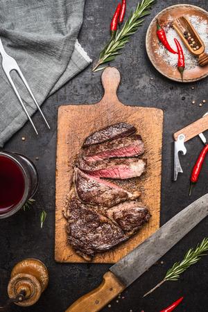 cuchillo: En rodajas excelente carne de solomillo medio raro a la parrilla de barbacoa de res a bordo de corte en el fondo de la cocina r�stica con el cuchillo, especias y vaso de vino tinto. Vista superior