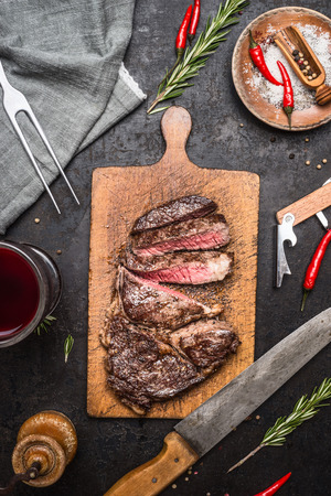 rustic: Sliced excellent  medium rare grilled beef barbecue Sirloin steak  on cutting board on rustic kitchen background with knife, spices and glass of red wine. Top view Stock Photo