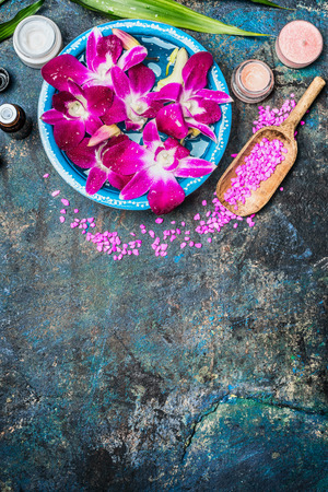 Wellness or spa background with pink orchid flowers  in bowl with water, shovel of sea salt, cream jar , candles and green bamboo leaf . Top view, place for text. Stok Fotoğraf