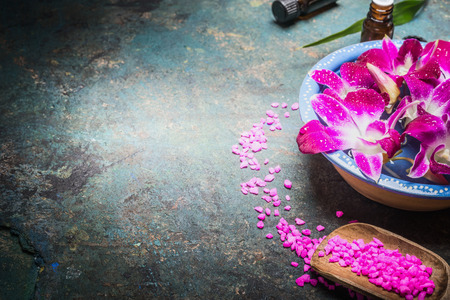 Bowl with water and purple orchid flowers on dark background with shovel of sea salt. Spa, wellness or body care concept. Stock Photo