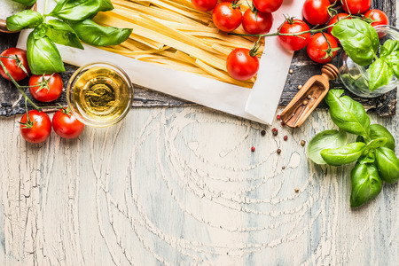 Pasta with fresh tomatoes, basil and olive oil on light shabby rustic background, top view, border. Tagliatelle pasta with ingredients for cooking. Italian food. Stock Photo