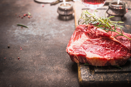 Close up of raw fresh meat Ribeye Steak with herbs and spices on dark rustic metal background, place for text. Stock Photo