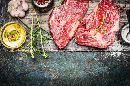 dark meat: Two raw steaks with oil and spices on dark rustic background, top view, border Stock Photo