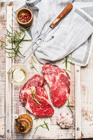 argentinean: Raw fresh marbled fillet steaks with ingredients for grill or cooking on light rustic background, top view.  Argentinean fillet steak. Stock Photo