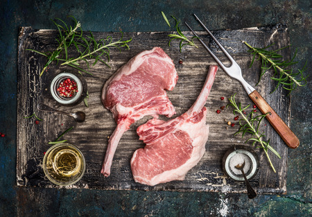 Raw pork cutlet with oil and spices for grill or cooking on rustic background, top view.  Porco Iberico French Racks.
