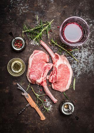 Raw Porco Iberico vlees ribben kotelet met ingrediënten en een glas rode wijn op rustieke metalen achtergrond, bovenaanzicht. Frenched Racks vlees Stockfoto