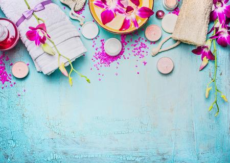 Spa oder Wellness mit rosa lila Orchidee blüht Einstellung, Schüssel mit Wasser, Handtuch, Creme, Meersalz und Naturschwamm auf türkisblauem Hintergrund, Ansicht von oben, Platz für Text. Körperpflege-Konzept