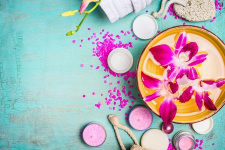 azul turqueza: Cuenco con agua y flores de orquídeas de color rosa con el bienestar y spa ajuste sobre fondo azul turquesa, vista desde arriba, de cerca. Foto de archivo