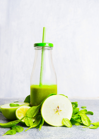 fruits juice: Green smoothie bottle with straw and green ingredients on light wooden background, side view. Healthy lifestyle and detox or diet  food concept