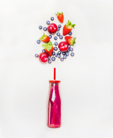 frutas: bebida batido en botella con paja y frutas bayas ingredientes sobre fondo blanco de madera, vista desde arriba