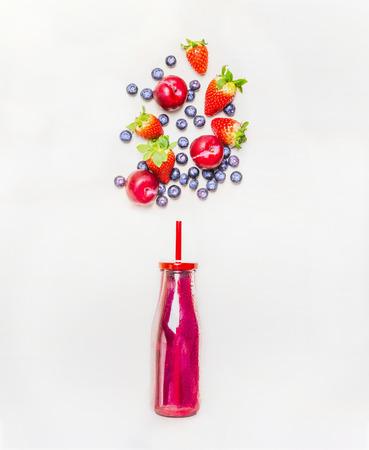 Rode smoothie drank in fles met stro en vruchten bessen ingrediënten op een witte houten achtergrond, bovenaanzicht
