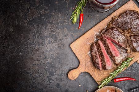 Gesneden middellange zeldzame gegrilde biefstuk op rustieke snijplank met rozemarijn en specerijen, donkere rustieke metal achtergrond, bovenaanzicht, plaats voor tekst