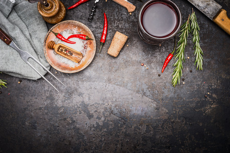 meat food: Food or cooking background with herbs , spices , meat fork and knife and glass of red wine on dark rustic metal background, top view, border Stock Photo