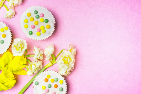 over white: Cake and daffodils flowers on pink background, top view, place for text. Easter bake