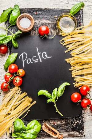 Pasta cooking background with chalkboard, tomatoes, basil and olive oil, top view. Italian food concept Stock Photo
