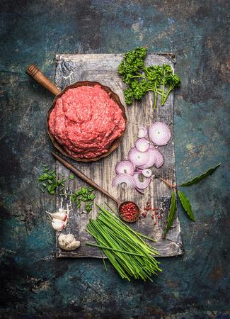 carne cruda: La carne picada en una sartén con ingredientes de cocina y cuchara de madera en el fondo rústico oscuro, vista desde arriba