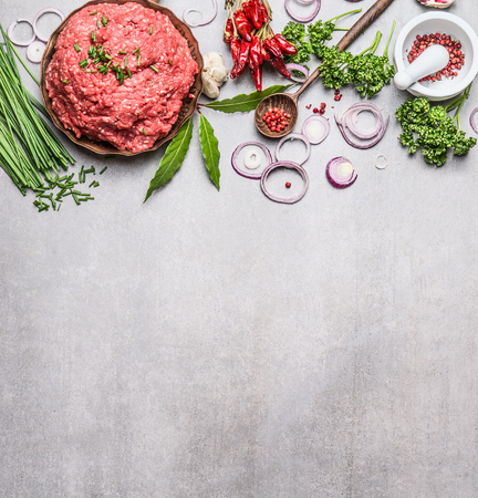 light slate gray: Organic Minced Meat with cooking ingredients , wooden spoon and spices mortar  on gray stone background, top view, place for text. Meat food