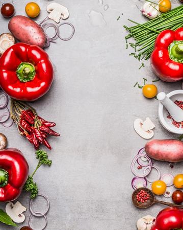 cebolla blanca: pimentón rojo y diversas verduras y los ingredientes para cocinar sobre fondo gris piedra, vista desde arriba, marco, vertical. La comida vegetariana y el concepto de estilo de vida saludable. Foto de archivo