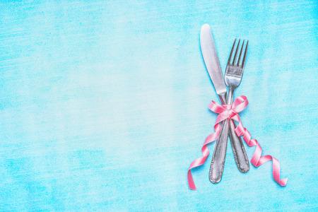 Bestek set met roze lint op lichtblauwe achtergrond, bovenaanzicht, plaats voor tekst. Tabel plaats instelling. Stockfoto