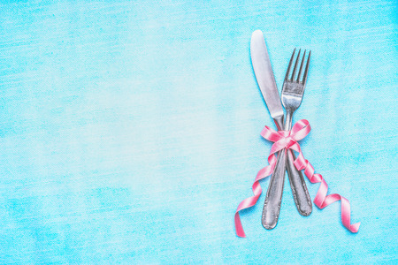 Cutlery set with pink ribbon on light blue background, top view, place for text. Table place setting.