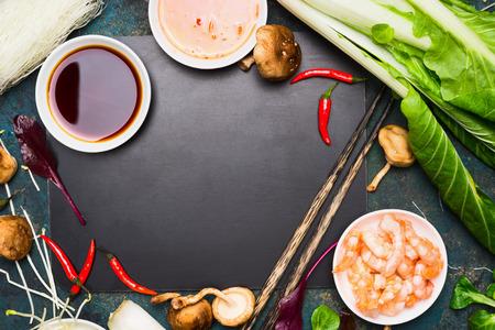 Chinese of Thaise keuken voedsel achtergrond. Aziatisch voedsel ingrediënten: sojasaus, eetstokjes, rijst, noedels, pok choi, shii-take paddestoelen en scampi op zwart leeg bord, bovenaanzicht. Stockfoto