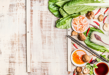 Chinese or Thai food background with Asian cooking ingredients, light rustic background, top view.