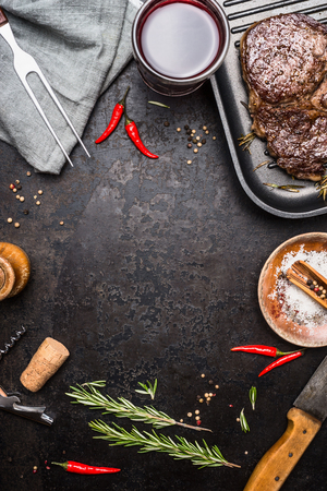 Food background with grilled Steak Ribeye on grill iron pan on rustic metal background with red wine, herbs and spices, top view
