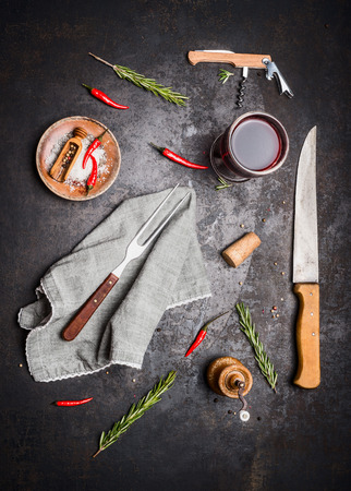 dark red: Flat lay with kitchen cooking tools, glass of red wine, herbs and spices on dark rustic background, top view